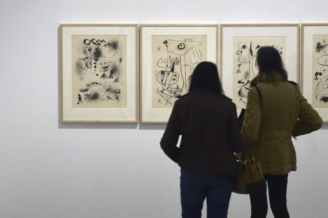 Des visiteurs observent les oeuvres de Joan Miro.... (PHOTO AFP)