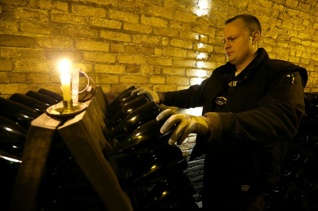 Un «remueur» de champagne à l'oeuvre chez Krug... (PHOTO AFP)