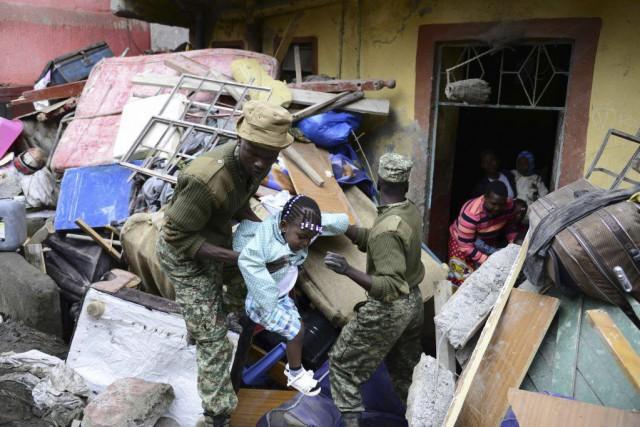 Des secouristes évacuent une fillette d'un immeuble qui... (PHOTO JOHN MUCHUCHA, AFP)