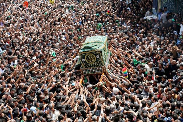 Les pèlerins suivent la réplique d'un cercueil transporté... (PHOTO THAIER AL-SUDANI, REUTERS)