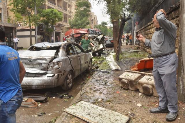 Des résidants d'Alep observent les dommages causés par... (PHOTO GEORGE OURFALIAN, AFP)