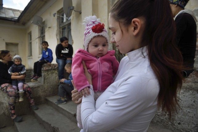 Lorena, 15 ans, tient dans ses bras son... (AFP, Daniel Mihailescu)