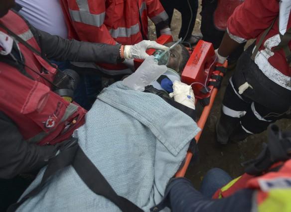 La première des quatre personnes rescapées des décombres... (AFP, Tony Karumba)