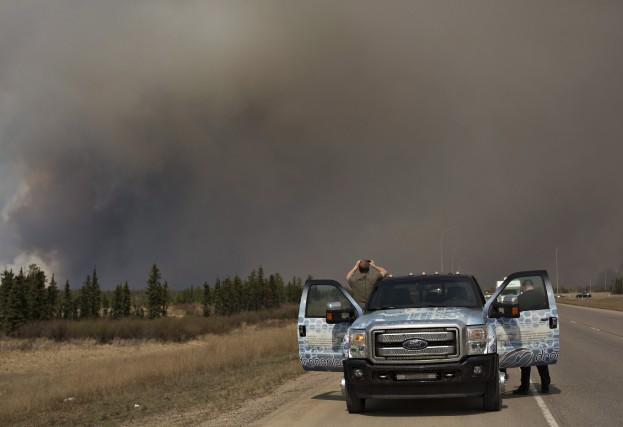 Les nuages de fumée et de cendres encerclent... (La Presse Canadienne)