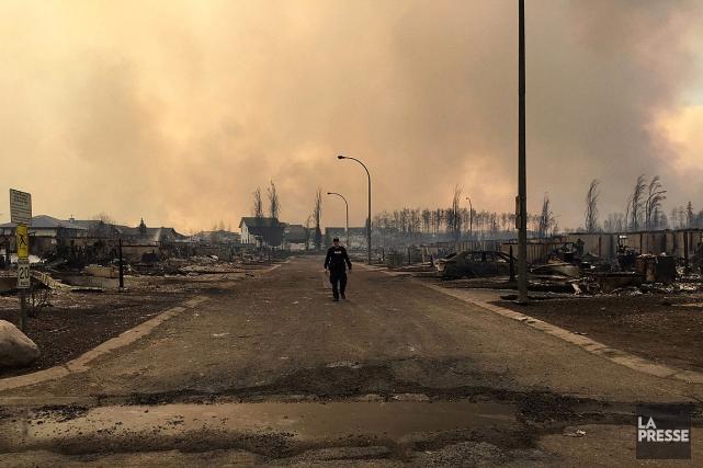 Un policier circule dans un quartier en ruine... (Photo fournie par la Police de l'Alberta)