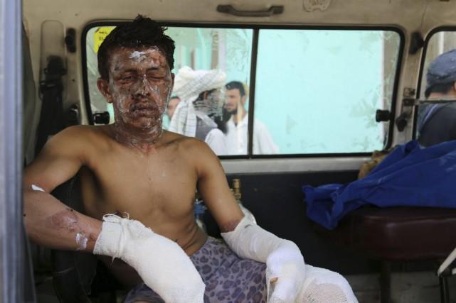 Un homme blessé est assis dans une ambulance... (PHOTO SAYED ZAKERIA, AGENCE FRANCE-PRESSE)