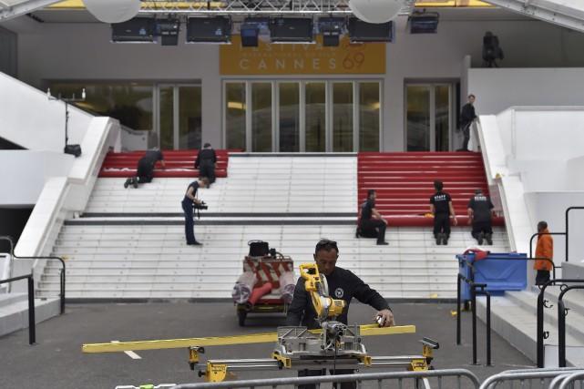 Les ouvriers installent le tapis rouge du palais... (Agence France-Presse, Loic Venance)