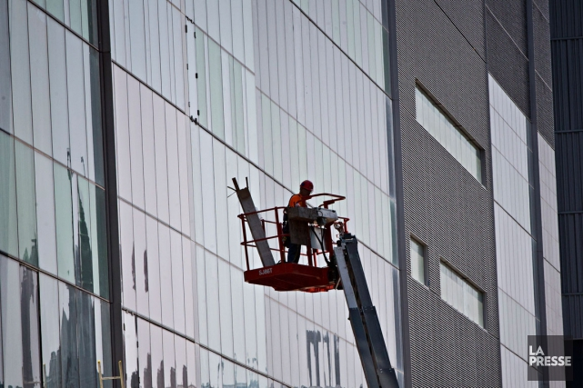 Un travailleur dans une nacelle contenant un poutre... (PHOTO PATRICK SANFAÇON, LA PRESSE)