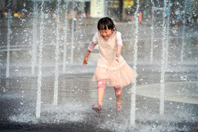 Une fillette se rafraîchit dans une fontaine du... (PHOTO BERNARD BRAULT, LA PRESSE)
