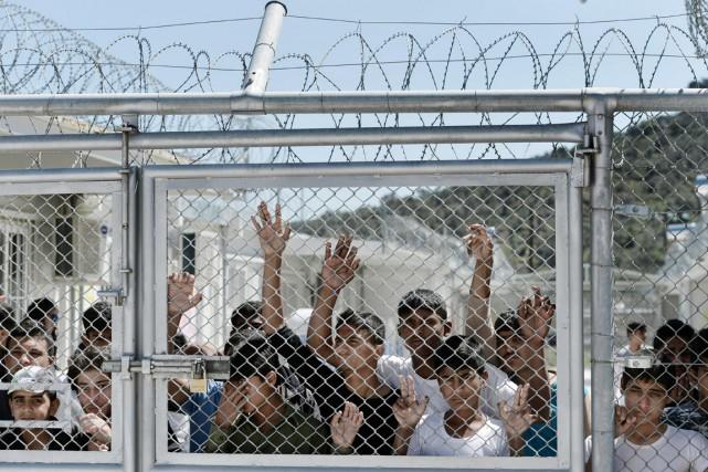 De jeunes migrants sont massés à une barrière... (PHOTO ARIS MESSINIS, ARCHIVES AFP)