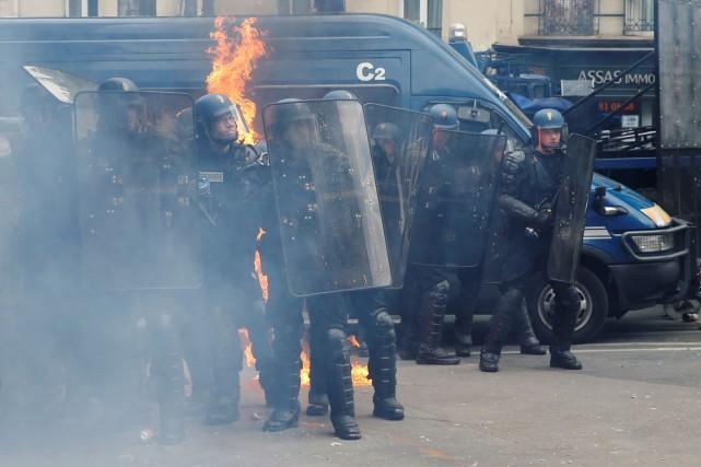 Des gendarmes se protègent d'un cocktail molotov qui... (PHOTO AFP/LIONEL BONAVENTURE)