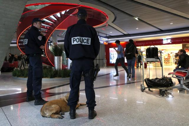 La police patrouillait jeudi l'aéroport Charles de Gaulle... (AP, Christophe Ena)