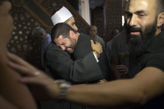 Un imam console un homme qui a perdu... (Photo AP)