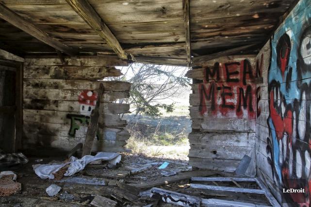 Les deux maisons, partiellement recouvertes de graffitis, sont... (Patrick Woodbury, LeDroit)