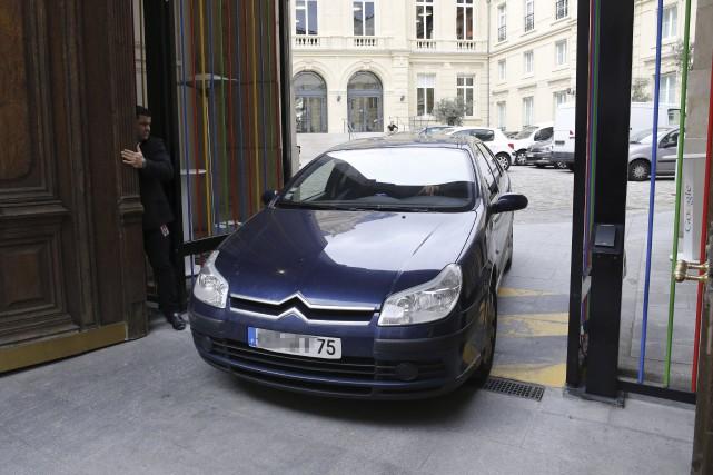 Une voiture de police quitte les bureaux de... (AFP, Matthieu Alexandre)