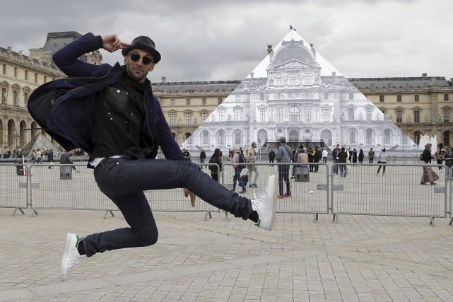 L'artiste français JR saute devant la Pyramide du... (AP, François Mori)