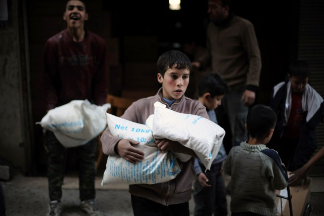 Un jeune Syrien transporte un sac d'aide alimentaire... (PHOTO AMER ALMOHIBANY, ARCHIVES AFP)