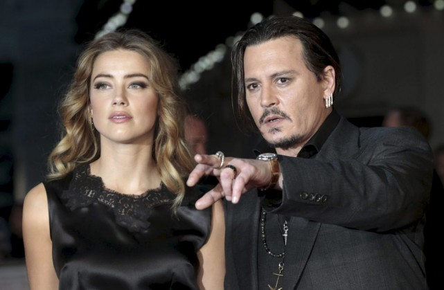Johnny Depp et sa femme, l'actrice Amber Heard.... (PHOTO SUZANNE PLUNKETT, ARCHIVES REUTERS)