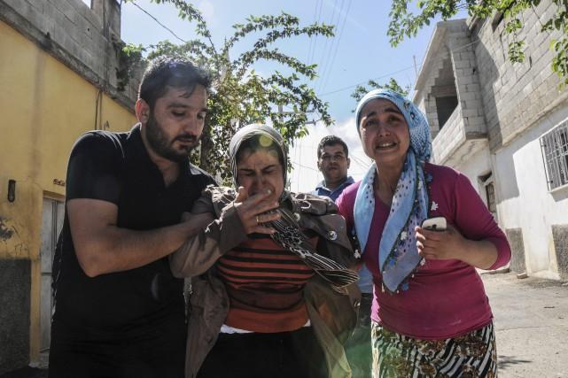 Des résidents se sauvent alors que la Syrie... (AFP)