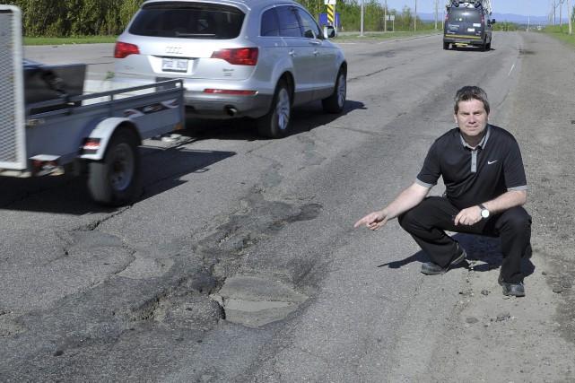 Carl Dufour montre l'état du boulevard Saguenay.... (Photo Le Progrès-dimanche, Rocket Lavoie)