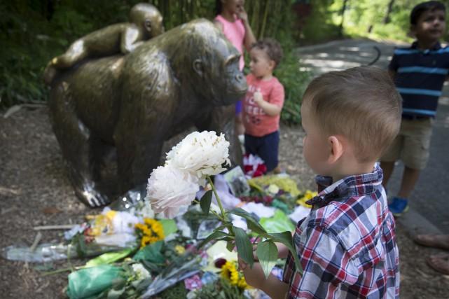 Un enfant dépose des fleurs près d'une statue... (AP, John Minchillo)