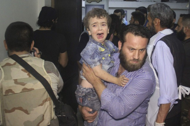 Un homme transporte à l'hôpitalun enfant en larmesaprès... (AFP, Omar haj kadour)
