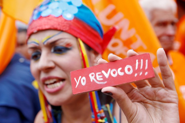 Une partisane de l'opposition tient un écriteau miniature... (PHOTO Carlos Garcia Rawlins, REUTERS)