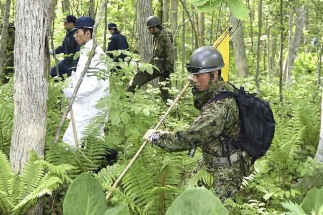 Des militaires et des civils tentent de retrouver... (Kyodo News via AP, Daisuke Suzuki)