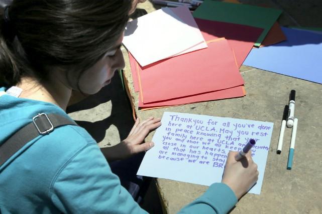 Une étudiante écrit un mot en hommage à... (AP, Nick Ut)
