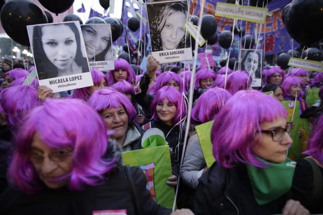 Des manifestantes tiennent des photos de femmes victimes... (Photo Victor R. Caivano, AP)