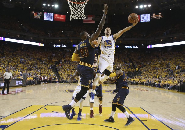 LeBron James (23) des Cavaliers tente d'empêcher Stephen Curry... (AP, Ezra Shaw)
