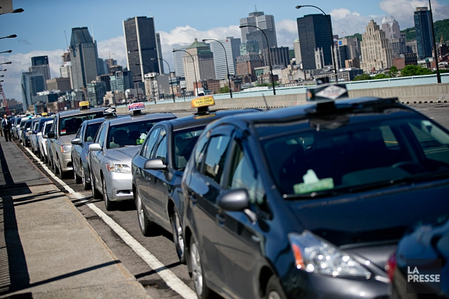 Plusieurs dizaines de voitures de taxi ralentissaient la... (PHOTO DAVID BOILY, LA PRESSE)
