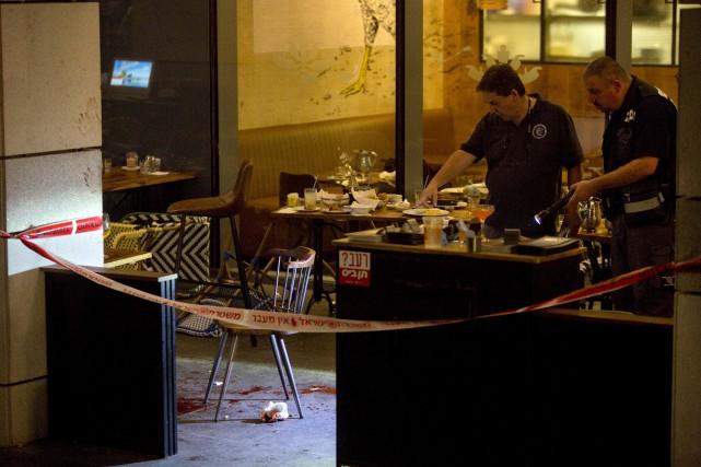 Deux policiers examinent la scène de l'attentat qui... (AP, Sebastian Scheiner)