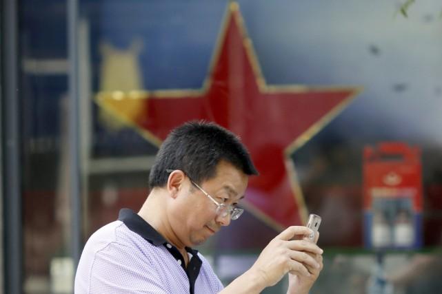 Un homme consulte son téléphone intelligent devant une... (PHOTO Ng Han Guan, ARCHIVES AP)