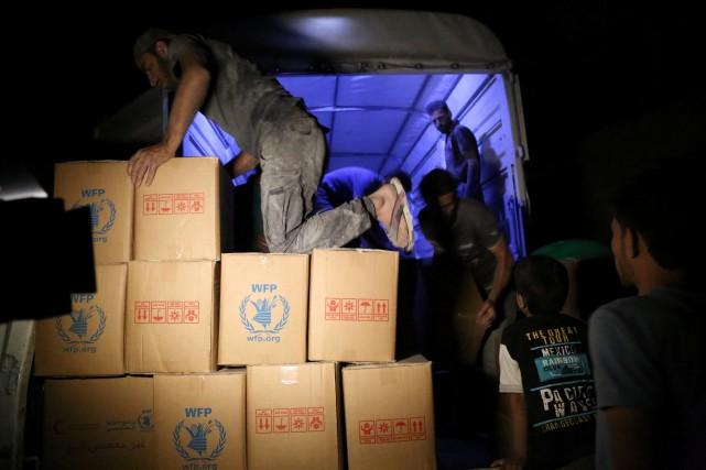 Des employés déchargent des cartons d'aide destinés à... (Photo Hussam Al Saleh, PAM via Reuters)
