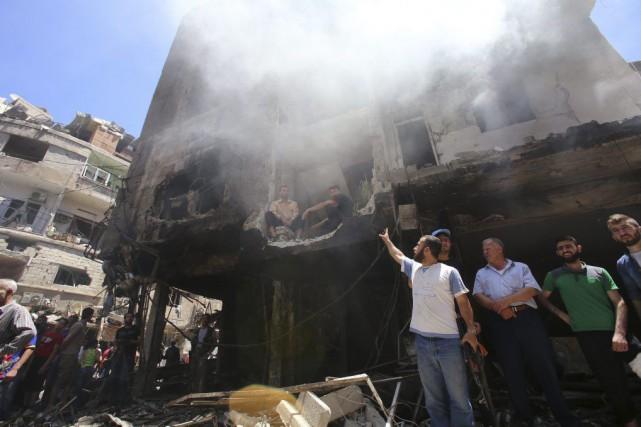 Des Syriens examinent les décombres non loin du... (PHOTO YOUSSEF KARWASHAN, AFP)