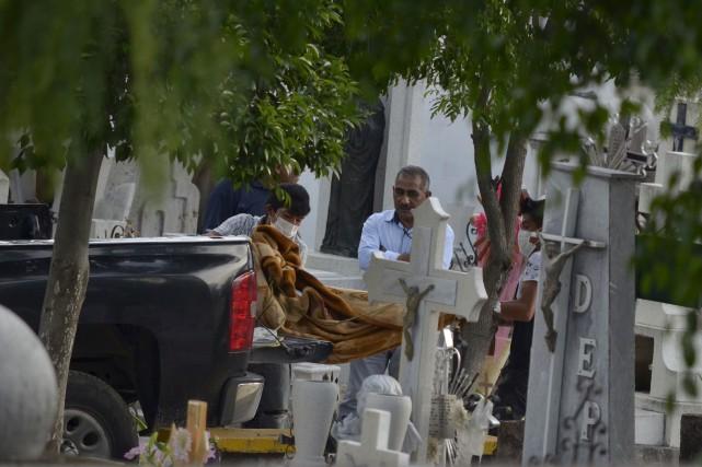 Des travailleurs transportent les corps de la famille... (Associated Press)