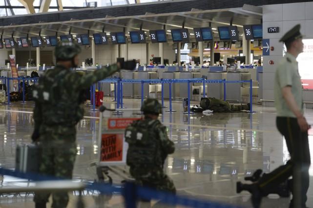 Un artificier inspecte un bagage suspect à l'aéroport... (AFP)