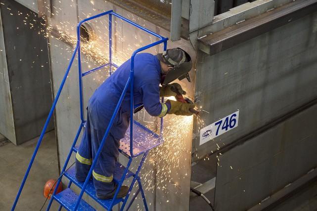 Un travailleur meule une soudure sur une composante... (La Presse Canadienne, Andrew Vaughan)