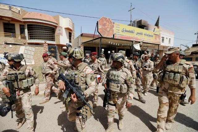 Des soldats irakiens lourdement armés patrouillent dans le... (PHOTO Thaier Al-Sudani, REUTERS)