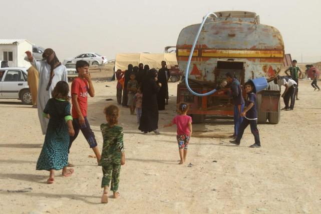 Des Irakiens déplacés attendent qu'on leur distribue de... (Photo MOADH AL-DULAIMI, AFP)