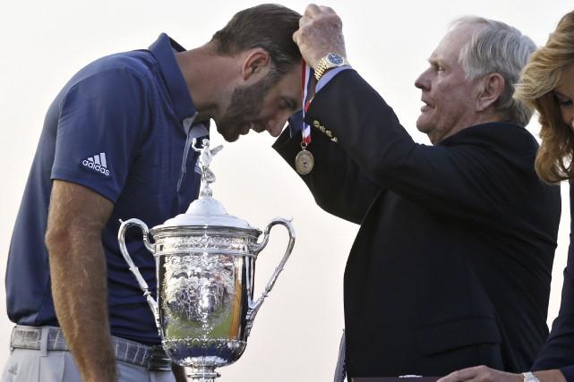 Dustin Johnson a reçu la médaille du vainqueur... (AP, John Minchillo)