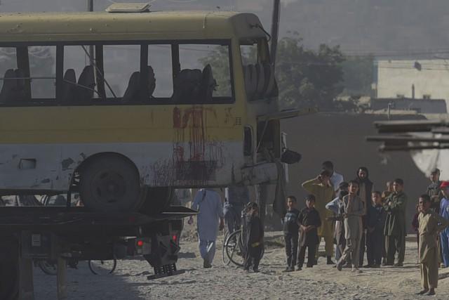 Des Afghans observent les autorités policières transporter un... (Agence France-Presse, Shah Marai)