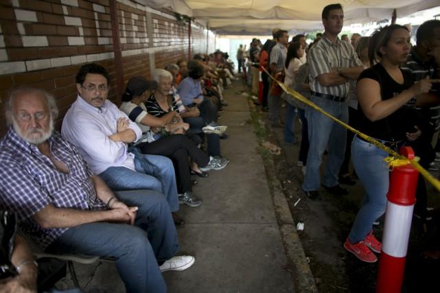Des milliers de Vénézuéliens faisaientdes files d'attente, lundi,... (AP, Ariana Cubillos)