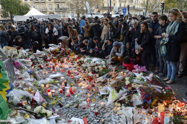 Des personnes se recueillent devant un mémorial en... (PHOTO MIGUEL MEDINA, ACRHIVES AFP)
