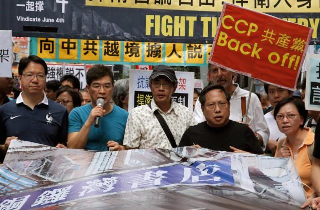 Récemment libéré, le librairie Lam Wing-kee (au centre)... (PHOTO KIN CHEUNG, ASSOCIATED PRESS)