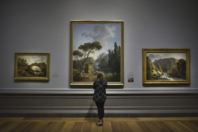 Une femme observe la toile Démolition du Château... (PHOTO AFP)