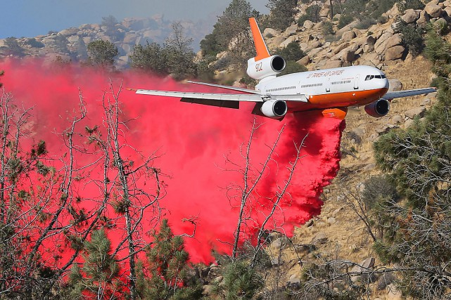 Un avion survole la zone du feu d'Erskine... (Photo Casey Christie, The Bakersfield Californian via AP)