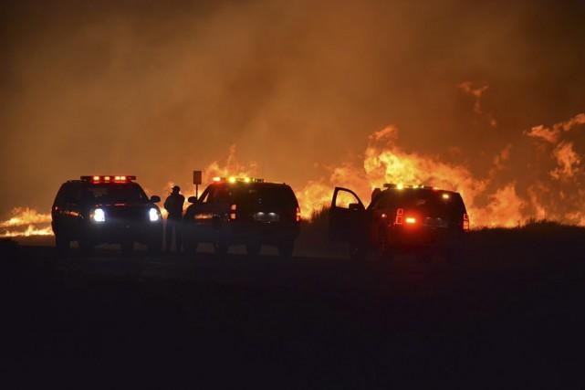 Les pompiers et les policiers surveillent l'incendie de... (Agence France-Presse)