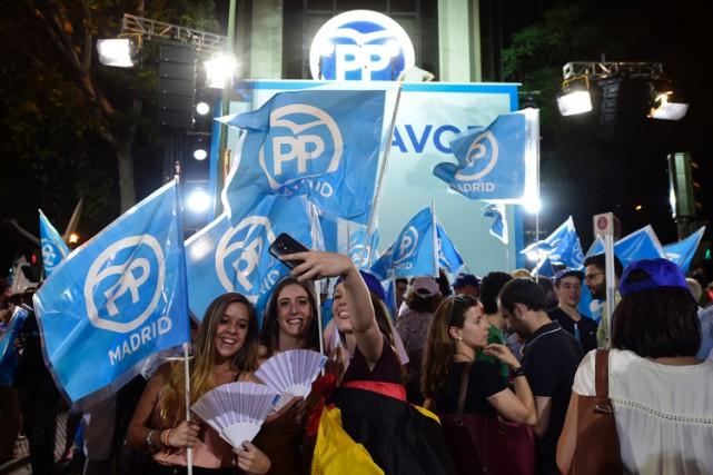 Des supporters du Parti populaire célèbrent la victoire... (PHOTO AFP)